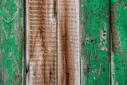 The texture is an old wood, damaged with cracked paint, with holes. Brown and green. Wallpaper, background