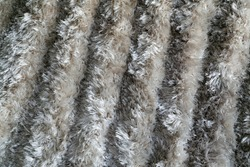 The texture of a long pile of gray artificial carpet. Domestic rug texture. Focus with a shallow depth of field. Polypropylene long pile carpet, close-up. Floor covering made of pvc threads.