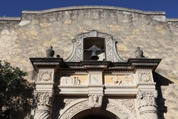The texture of a rock wall and ornate stonework at the entrance of The Alamo in San Antonio, Texas