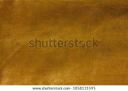 The texture of a thin nylon transparent fabric close-up in Fortuna Gold color. Pattern, background in color trend 2021 Foto stock ©