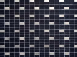 The texture of black and white ceramic tiles or smooth brickwork. Example of a background with different uneven lighting.