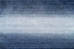 The texture of blue jeans with a light white stripe in the middle of the denim fabric for the background.