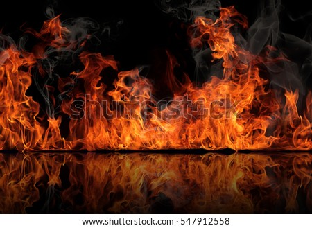 The texture of fire on a black background is reflected in a glossy table. #547912558