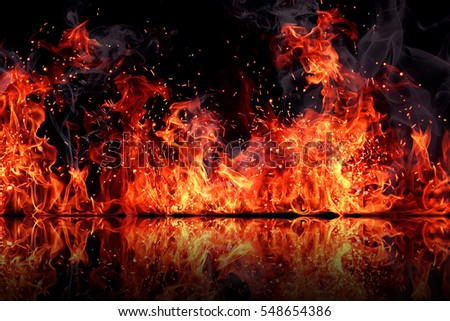 The texture of fire on a black background is reflected in a glossy table. #548654386