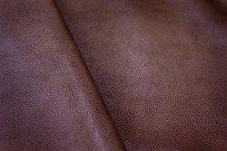 The texture of leather with free space for text. The skin is laid in folds. Genuine leather for furniture. Red leather.