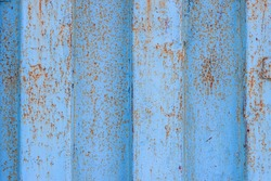 The texture of rusted metal painted in blue. Rough metal surface with rust. Rusty metal wall of a shipping container. Perfect for background and design.