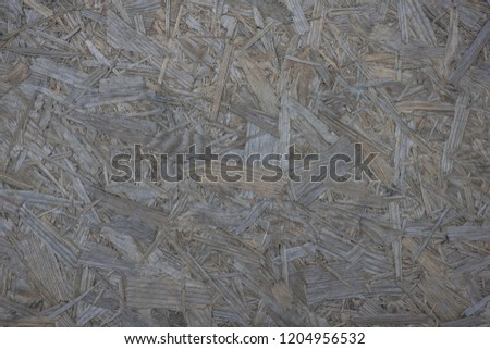 The texture of sawdust, small chips, lumber. Gray plywood, calm background. Without picture.