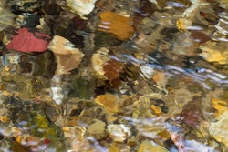 The texture of the colored stones under water. A ray of sun is playing on the surface of the water. Polished pebbles are visible under the water.