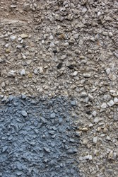 The texture of the concrete part of the wall with a gray spot. Gray Cement wall background textured with stone chips. Concrete wall of a building with stones of different sizes, Vertical photo