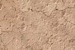 The texture of the concrete wall with irregularities, cracks, painted in sand color. Abstract background.