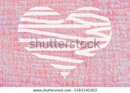 The texture of the fabric is pink or coral. Heart of lighter color abstract. Background for Valentine's Day. Valentine's Day celebration.