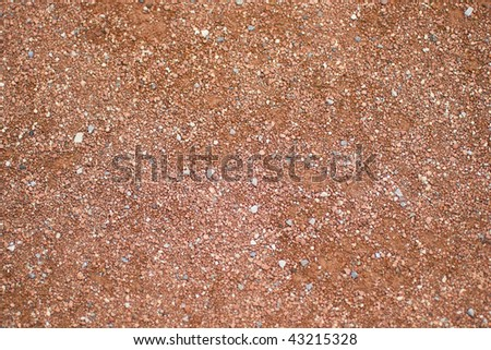 The texture of the infield of a baseball diamond, made up of crushed stone and a reddish brown clay.