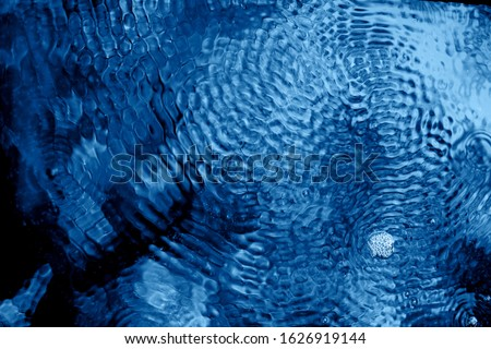 Photo of  The texture of the ripples on the water.From of vibration, pulsation.Classic blue. The 2020 trend.
