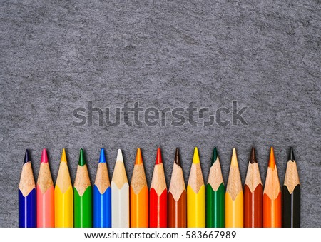 The texture of the school supplies on the graphite board closeup. Bright colorful  pencils on a dark gray background. Ready background for design                               #583667989