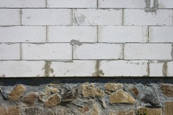 The texture of the stone foundation of the house along with the wall. Close-up