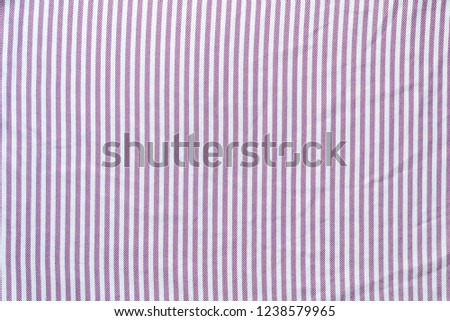 The texture of the striped fabric. Textiles for shirts in lilac stripes. Smooth cloth swatch #1238579965