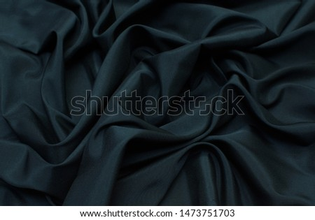 The texture of the synthetic fabric is dark green. Background, pattern. #1473751703