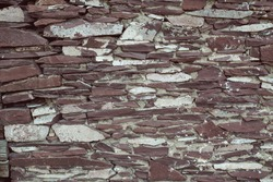 The texture of the wall is made of natural stone flagstone. Vintage stonework, vintage background. The wall is made of stone slabs