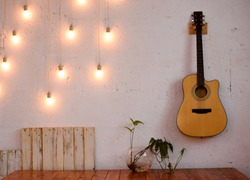 The textured white wall is decorated with yellow lights and a guitar.