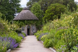 The 19th Century thatched round house surrounded by beautiful flower beds and gravel paths in the walled garden at West Dean gardens in West Sussex, England