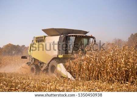 The theme is agriculture. A modern combine harvester in the field performs grain harvesting on a sunny day against a blue sky. Farm and automation using machines #1350450938