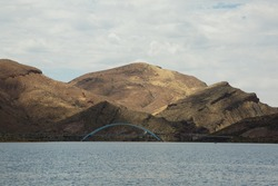 The Theodore Roosevelt Lake Bridge stands in the shadow of the mountainous landscape