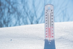 The thermometer lies on the snow and shows a negative temperature in cold weather on the blue sky.Meteorological conditions with low air and ambient temperatures.Climate change and global warming