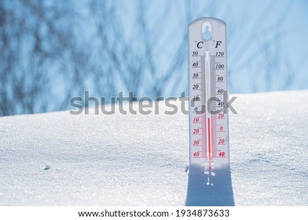 The thermometer lies on the snow and shows a negative temperature in cold weather on the blue sky.Meteorological conditions with low air and ambient temperatures.Climate change and global warming Foto stock ©