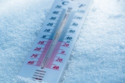 The thermometer lies on the snow in winter showing a negative temperature. Meteorological conditions in a harsh climate in winter with low air and ambient temperatures.Freeze in wintertime