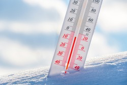 The thermometer lies on the snow in winter showing a negative temperature.Meteorological conditions in a harsh climate in winter with low air and ambient temperatures.Freeze in wintertime.Sunny winter