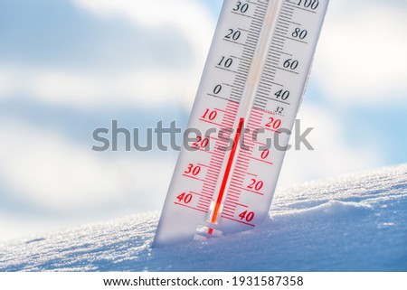 The thermometer lies on the snow in winter showing a negative temperature.Meteorological conditions in a harsh climate in winter with low air and ambient temperatures.Freeze in wintertime.Sunny winter Foto stock ©