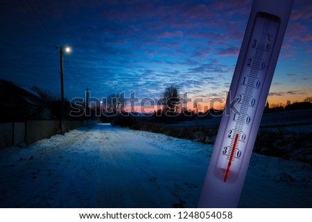 The thermometer on the background of the winter landscape in winter shows a temperature of minus 17 degrees Celsius, a decrease in temperature