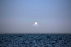 The thick fog partially obscures the lighthouse on Lake Michigan
