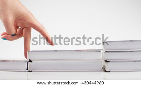 The thirst for knowledge. Self. A staircase made of books. The hand is symbolizing the man climbs up the stairs of books on white background