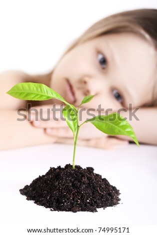 The thoughtful girl looks at a young plant