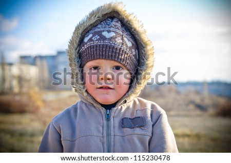 The thoughtful little boy on walk in the autumn in a hood on the nature
