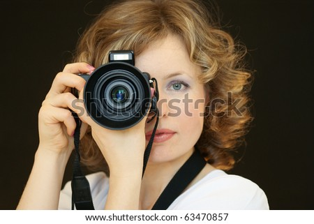 The thoughtful young woman holds a digital camera in a hand