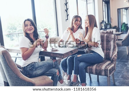 The three best girlfriends gathered to drink coffee and gossip. Girls having fun and laughing.