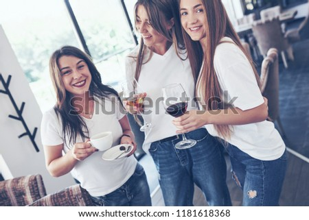The three best girlfriends gathered to drink coffee and wine. Girls having fun and laughing.