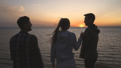 The three friends standing on the sea shore on the sunset background