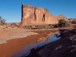 The Three Gossips Monument in Arches National Park, Utah, photographed with sand and a pool of water in the foreground.