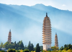 The Three Pagodas of Chongsheng Temple near Dali Old Town, Yunnan province, China. Scenic mountains are visible in background. Ancient pagodas are a popular tourist destination of Asia.