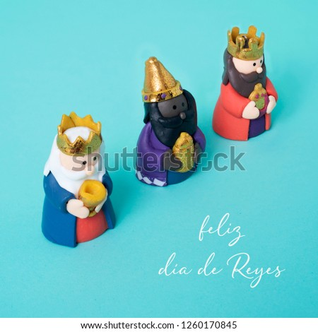 the three wise men and the text feliz dia de reyes, happy epiphany day written in spanish, on a blue background