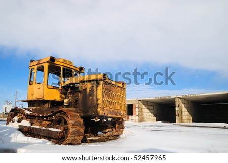 The thrown yellow tractor against the cloudy sky. Winter
