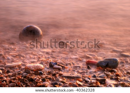 The tide coming in on a pebble beach.