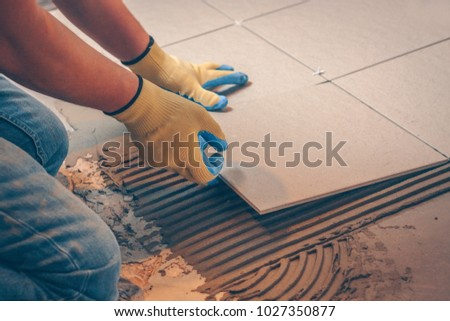 The tile glues the tile to the floor with a glue applied by a notched trowel #1027350877