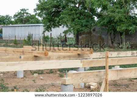 The timber framing of a A-type house under construction on a pile foundation. Pile foundation construction frame house.