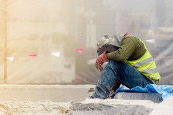 The tired construction worker in the green waistcoat and the red glove sitting on the concrete ground in the construction area