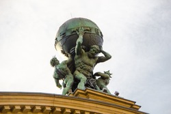 The titan called Atlas is carrying the world on his shoulders. Greek mythotology figure as  part of the historical train station roof built in 1888 in Frankfurt, Germany.