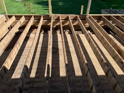 The top down view of the foundation of a wooden deck in a backyard. The structure is what remains after deconstructing the flooring. The wood is old, weathered, and full of green mold.